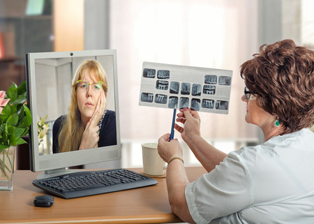 Young woman suffers toothache in monitor of online female dentist which exams at x-ray image of teeth Stock Photo