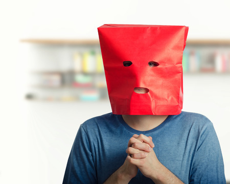 awkward: Hard introverted guy feels awkward. He clenches hands and looks at camera with red paper bag over head