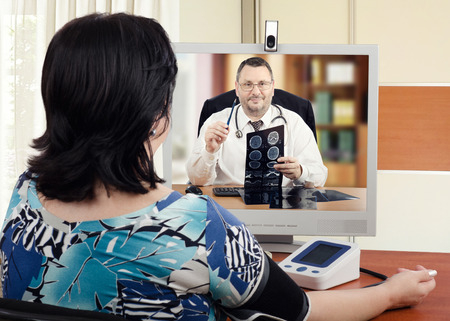 Telehealth cardiologist sits face to face with online female patient which measures her blood pressure. Virtual doctor attentively describes brain x-ray results to her