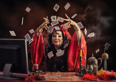 Mature Gypsy fortune-teller sitting opposite monitor tossing playing cards up to predict future for her online customer Stock Photo