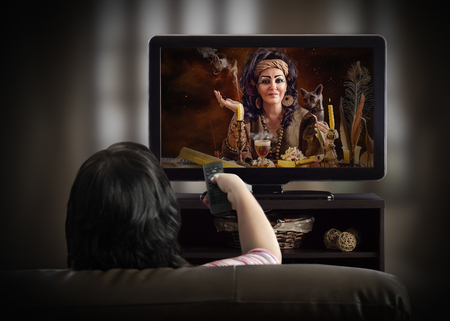 Back view on woman in couch watching esoteric TV channel with Egyptian psychic