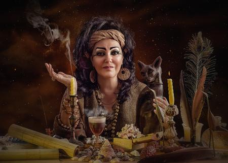 soothsayer: Madura astrólogo egipcio posando con la figurilla gato y artículos mística. El adivino se sienta en el mostrador de atención mira a la cámara