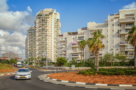 Rishon LeZion, Israel-May 27, 2016:  Traffic circle with young palm trees on Menachem Begin Road. There are white multi-story residential apartment buildings on blue sky background