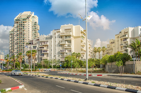Rishon LeZion, Israel-May 27, 2016:  White multi-story residential buildings are flooded with warm early sunset light. Wide shot on blue sky background