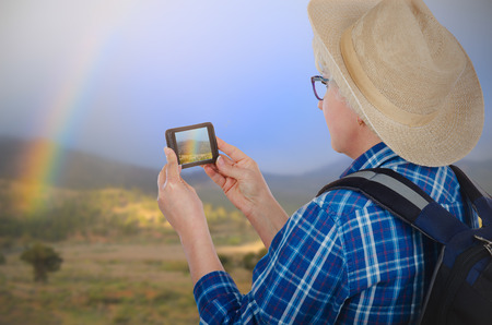 Hiking adult woman in yellow hat captures photo of rainbow with mobile phone.  Travel concept. Back view Stock Photo