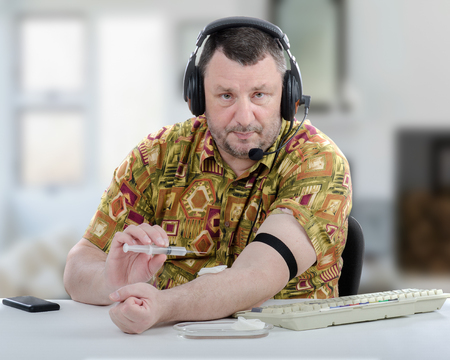 Man in headset intend to inject medication into his vein at the first time. Telehealth concept Stock Photo