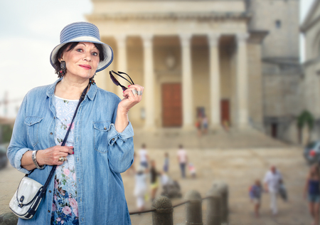 Pleasant senior woman in denim clothes traveling in Europe. She posing on blurred background of old building with columns. Woman wears striped bucket hat, coat, cross body bag. Her right hand holds sunglasses. Travel concept. Mid-shot portrait.