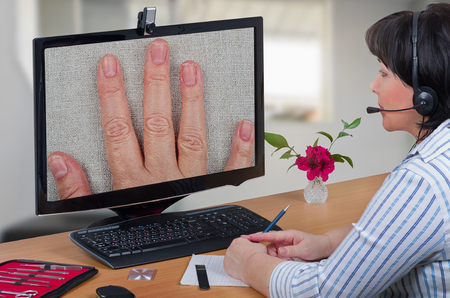 Telehealth female dermatologist in headset looks at peeling off nails layers of female patient on monitor with attention.  Virtual doctor sees falling off fingernails either by online video chat or snapshot. Horizontal mid-shot on blurry indoors backgroun
