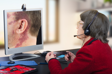 Telehealth female dermatologist in headset observes at birthmark on computer monitor attentively.  Virtual doctor looks at man having a big red birthmark on his face and neck either by online video chat or snapshot. Horizontal mid-shot on blurry indoors b Stock Photo