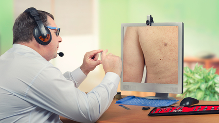 Telehealth male dermatologist in headset looks at sebaceous cyst on back of the patient on monitor carefully.  Virtual doctor sees wen on mans skin either by online video chat or snapshot. Horizontal mid-shot on blurry indoors background Stock Photo