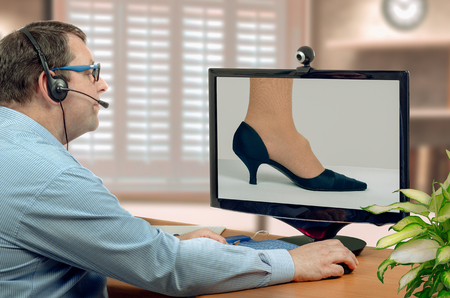 orthopedist: Telehealth male orthopedist in headset looks at foot hygroma of female patient on monitor thoughtfully.  Virtual doctor sees cystic tumor either by online video chat or snapshot. Horizontal mid-shot on blurry indoors background Stock Photo