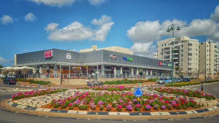 ner: Nes Ziona, Israel-March 20, 2016:  Beautiful view of big flowerbed placed on traffic circle in front of supermarket Mega In The City and other commercial stores. Nice blue sky is over it. The complex is located at 1 Avner Ben Ner Street. Two white multi-s
