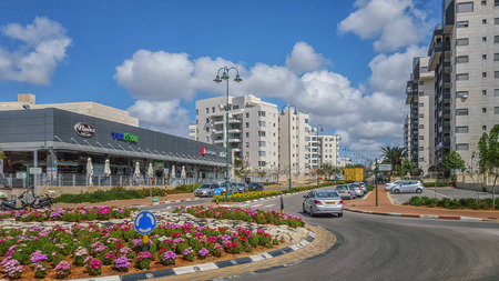 ner: Nes Ziona, Israel-March 20, 2016: Front view of beginning of Avner Ben Ner street. New modern multi-story residential buildings are located on both sides of it. There are supermarket and other commercial stores in left side and beautiful traffic circle in Editorial