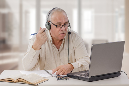 he: Old man in headset sits in front of notebook computer. He setts up his own online tutoring business