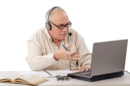 Retired man working as internet freelancer talks briskly with someone by notebook computer Stock Photo