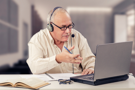 the elderly tutor: Retired man works as freelancer in internet from home office. He emotionally explains sitting in front of notebook computer Stock Photo