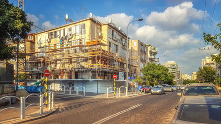 Rishon LeZion, Israel-August 14, 2016: Old shabby four-story residential building is fenced and framed with scaffolding involved in project TAMA 38. It will be tiled, build balconies and two floors Editorial