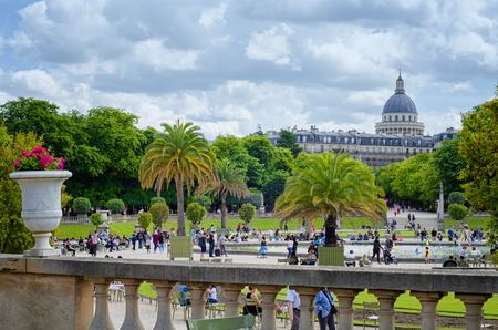 Paris, France - 5 juin 2017: Les gens se promènent autour d'un étang de voiliers dans les jardins du Luxembourg. Le dôme du Panthéon et la façade des bâtiments avec le toit du grenier sur la rue Gay-Lussac sont vus en arrière-plan sous un ciel nuageux Banque d'images - 85431749