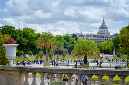 Paris,  France - June 5, 2017: People walk around sailboats pond in Luxembourg gardens. Pantheon dome and buildings facade with attic roof on Rue Gay-Lussac are seen in the background under cloudy sky