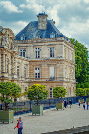 Paris,  France - June 5, 2017: Wing of famous Luxembourg Palace. South facade framed with metal fence with sharp spikes. There are trees growing in big crates and some people walking along of it