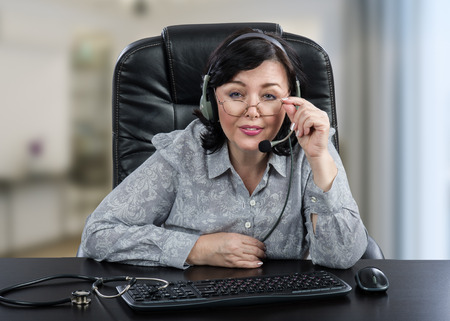 Surprised telemedicine consultant in headset touches glasses by left hand and looks at the camera attentively. Middle aged female doctor sits at black office desk with keyboard, mouse and stethoscope