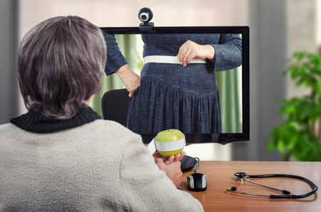 Remote nutrition adviser instructs how to measure body waist. For clear exposition telemedicine dietitian uses green apple. Patients body with white tailor meter is seen in her desktop monitor