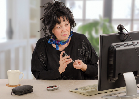 Mature woman learns to test blood sugar. Sitting patient watches video manual on computer monitor by online holding lancing device. On the desk there are blood glucose meter with cover and keyboard