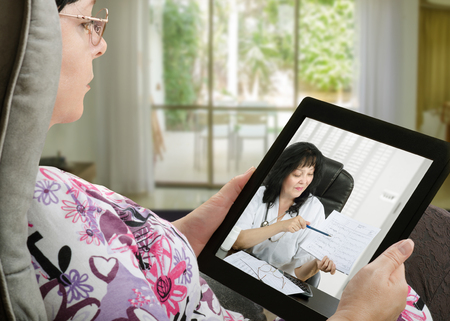 Mature adult woman consults a telemedicine doctor with tablet computer sitting in soft chair. In touchscreen, female doctor in white uniform reviewing blood pressure report. With telehealth application patient can reach relevant specialist remotely. Horizontal side shot on indoors blurred background