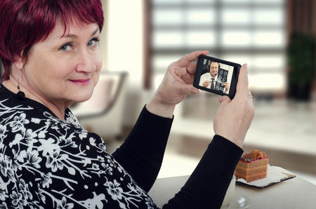 Senior woman holding mobile phone by hands. On the screen there is virtual doctor attentively reviews brain x-ray results. Telemedicine application gives the woman the convenience of seeing a doctor via her mobile phone sitting at cafe table.