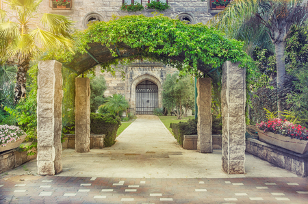 Entry arch on four columns covered by climbing plants is located in front of stone house. On either side of the wide pavement pathway that leads to closed arched door stand green palms shrubs and flowerbeds. Horizontal summer shot