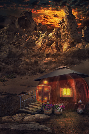 Warm yellow electric light shines out of pumpkin house window on the background of old crumbling mountains at the dusk time Stock Photo