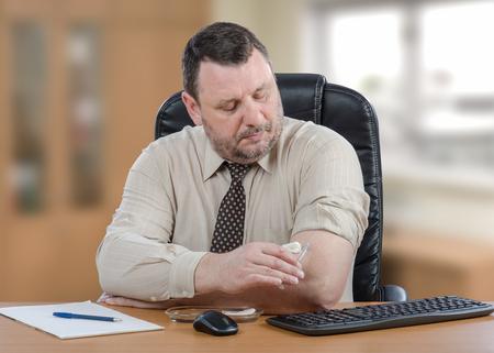 inyeccion intramuscular: El retrato del hombre de negocios consigue la autovacunación contra la gripe. Él sostiene la jeringa con la mano izquierda y mira el brazo derecho. Hombre de mediana edad sentado en el escritorio de oficina con teclado, mouse y cojín de papel.