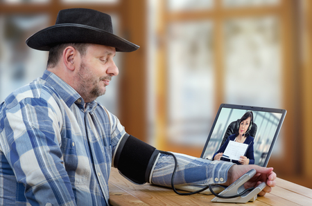 cowboy beard: Farmer consults a telemedicine specialist because he is not feels well. Middle-aged man suffers hypertension. Remote female doctor watches carefully at the patient and shows him results recent tests Stock Photo