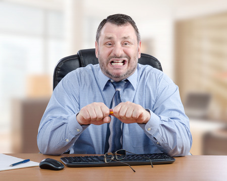 55 years old businessman has nervous breakdown. It seems something did made him angry. Bearded man in blue shirt screams and want to break pencil in his hands. He sits at wooden desk and looks at camera Stock fotó