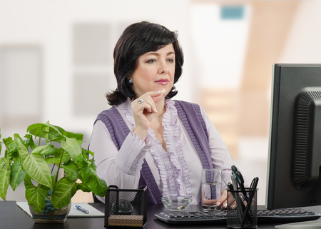 Middle aged business woman takes a pill during virtual doctor's appointment Stock Photo