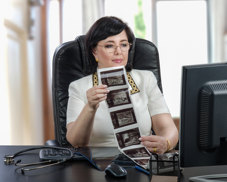 E-health female doctor holds ultrasound mammogram results looking at computer monitor. Telemedicine physician dressed a white blouse sitting at black desk in the office Stock Photo