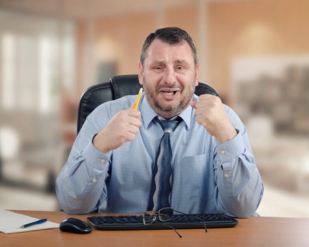 Panicked manager clenches his hands because he cannot make the right decision. Mature man wearing blue shirt and striped tie is ready to cry. He sits at wooden office desk Stock Photo