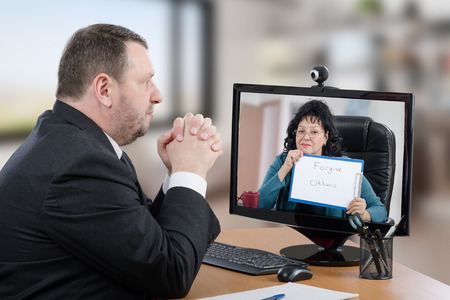 Telemental health patient suffering depression prefers consults psychiatrist from his office. Businessman in black suit sitting at desk attentively looks at virtual doctor on computer monitor