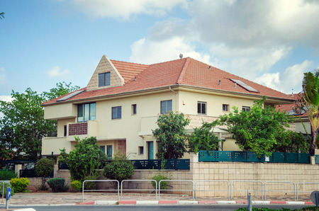 Rishon LeZion, Israel-May 20, 2017: 2-floor family private house under the sloping red-tiled roof. There are 2 solar panels and a penthouse above the main door of the house. The house is painted badge the yard fence is made of breaks tiled with yellow til