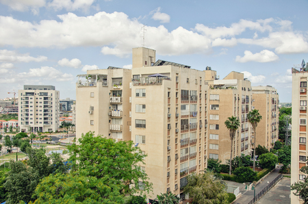 Ness Ziona, Israel-May 21, 2017:  The development of dwelling areas in the towns in middles 70s of 20 century have a specific feature of large tree zone round each dwelling block. The 3 yellow 8 floor residential buildings are almost sunk in green trees c