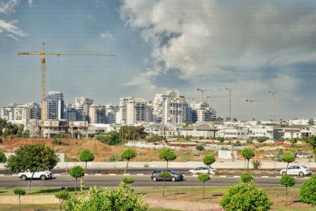 Rishon LeZion, Israel-June 17, 2017: New Nahlat Yehuda living district of white multi-floor living towers and some towers under the construction with lifting crane are at the remote rare sight.