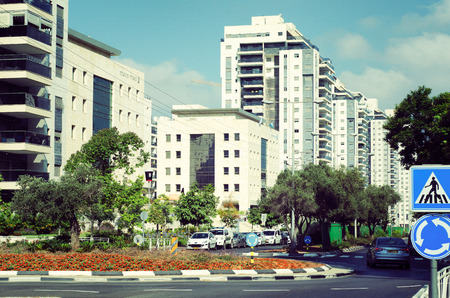 Rishon LeZion, Israel-June 17, 2017: A row of white high living towers is at the rare view. In front of the towers are two 6 story official building paneled with Jerusalem yellow sandstone. The traffic circle of Israel Galili St is at the front view. Editorial
