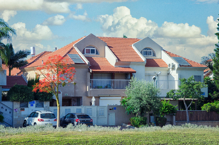 Rishon LeZion, Israel-June 10, 2017: Two-floor red roof private house of two separate living sections. The left section painted light brown the right one is white. Each section has a semi-recessed balcony with steel railing. There is a wide glass door to