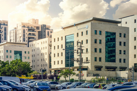 Rishon LeZion, Israel-June 17, 2017: TThe National Insurance Institute branch 5 levels official building for public acceptance. The construction of cast concrete tiled with decorative Israeli Jerusalem stone panels. Each central part of the building has a