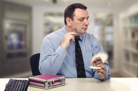 Middle age man in long-sleeve shirt and tie sits at the desk and injects some cosmetic stuff under his right eye socket. To control the process he looks at the portable mirror held in left hand. Banco de Imagens