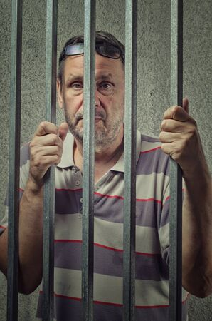 Portrait of an accused person in a pre-trial detention cell. Middle-aged unshaven man holds the prison bars with his hands and looks out through. Foto de archivo - 150083212