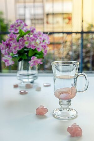 In Irish coffee mug preparing drinkable gem elixir. Burnished rose quartz stones are placed into distilled water. Two stone rabbits sit nearby it. Vase with flowers is seen on the balcony table. Archivio Fotografico