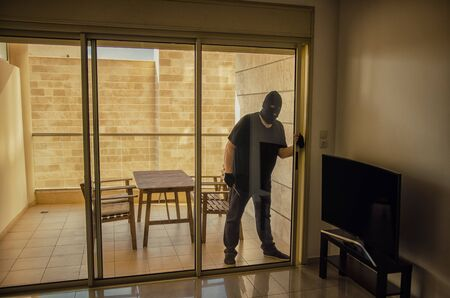 Thief in black balaclava comes inside the home because the homeowner forgot to close the sliding glass door in the balcony. Foto de archivo - 150107987