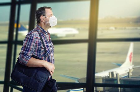 Mature man in a white face mask walking in an airport departure hall on the blurred wide window background with two airplanes there