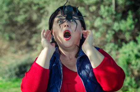 Mature woman in a red shirt and blue overcoat hikes in the garden and runs into a huge black spider.